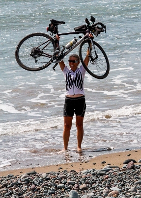 Lynn Salvo holds up her bike in triumph after setting a Guinness World Record on her ride for peace